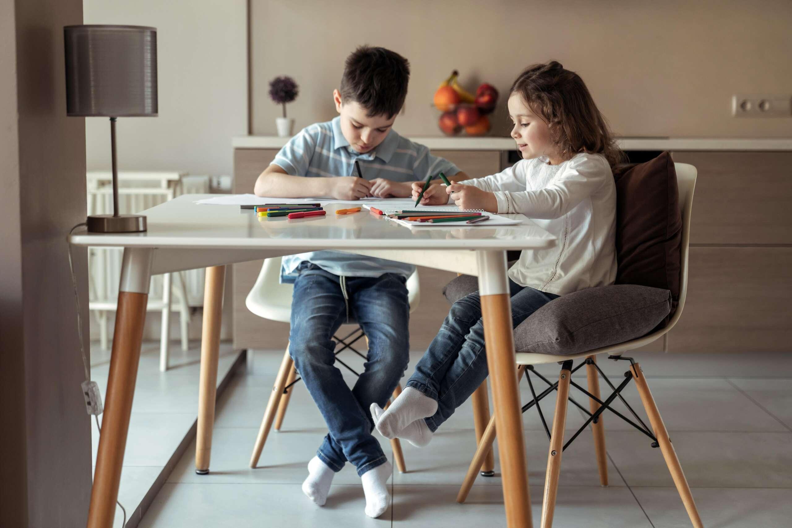 dzieci przy stole odrabiają lekcje